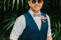 stylish navy pants, a waistcoat and a colorful bow tie plus a bright floral boutonniere for a summer or tropical look
