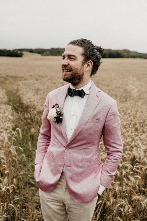 tan pants, a pink blazer, a polka dot black bow tie and a floral boutonniere for a chic summer groom's outfit