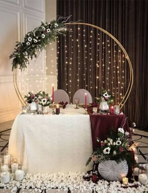 white blooms on the floor, candles, a lush and moody floral arrangement and the wedding arch with lights
