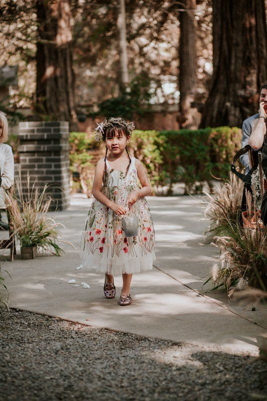 a beautiful floral embroidery A-line flower girl dress with no sleeves and a scoop neckline, shiny pink shoes and a floral crown
