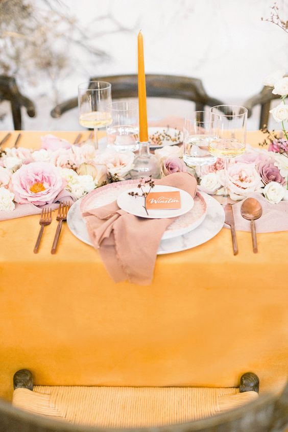 a beautiful spring wedding table setting with a yellow tablecloth and a candle, pink and blush blooms and a pink napkin