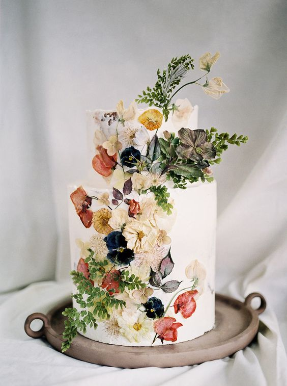a beautiful wedding cake inspired by Dutch Masters   a white wedding cake with pressed edible flowers and leaves is very chic