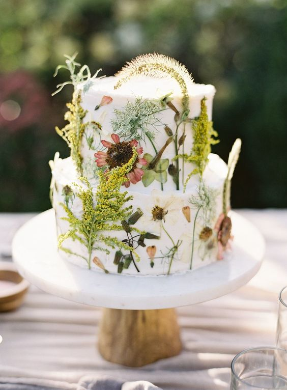 a boho summer wedding cake with lots of edible blooms and greenery pressed to it looks wild