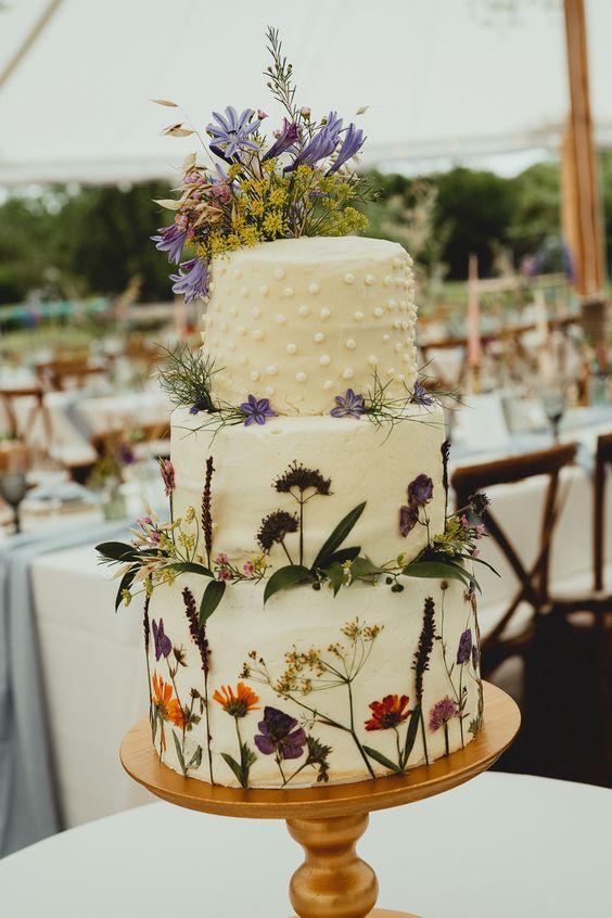 a boho wildflower wedding cake with lots of pressed edible blooms and leaves and polka dots on top