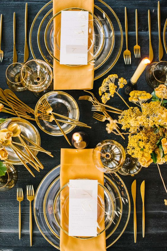 a bold and catchy spring tablescape with sheer glass plates, yellow napkins and blooms and gold cutlery is very modern