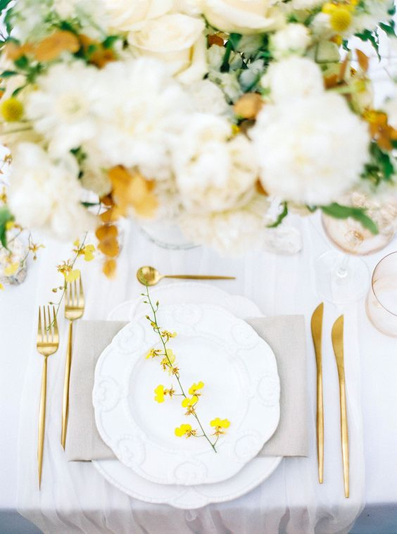 a bold spring wedding table setting with a grey napkin, a yellow blooming branch, gold cutlery and neutral blooms