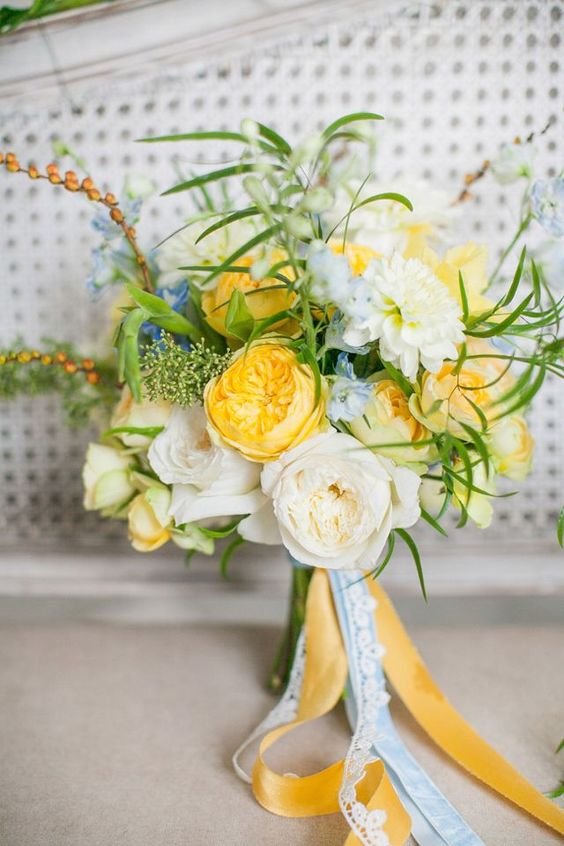 a bright and cool wedding bouquet with yellow and neutral blooms, touches of blue, greenery and long ribbons