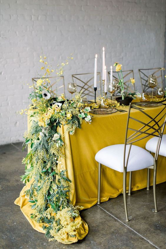 a bright and stylish spring wedding tablescape with a mustard tablecloth, bold yellow blooms and greenery and glass plates