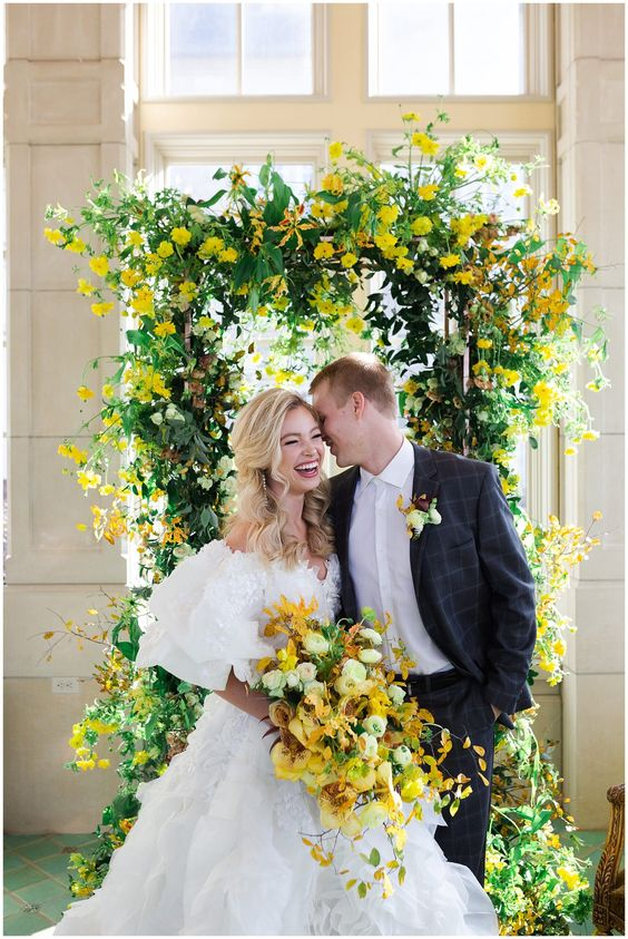 a bright wedding arch with much greenery and bold yellow blooms plus a matching wedding bouquet for spring