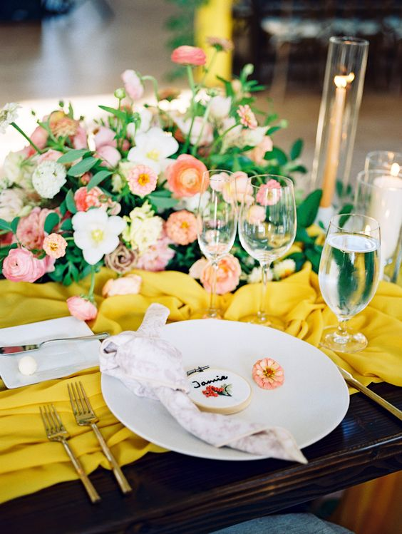 a bright wedding table setting with a yellow table runner, pink and red blooms, gold cutlery and a cookie