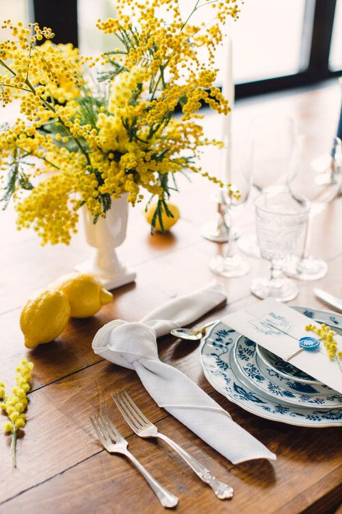 a bright wedding tablescape with a mimosa centerpiece and lemons, blue printed plates and white linens is chic
