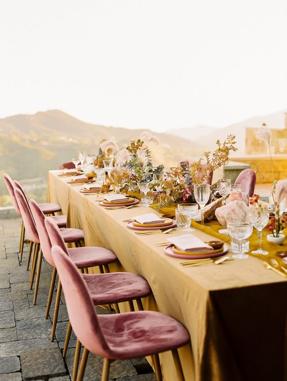 a bright wedding tablescape with mustard linens, blush plates, gold leaves and blooms and elegant glasses