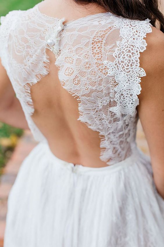 a chic A-line wedding dress with a lace bodice and a keyhole back on buttons plus a pleated layered skirt is cool