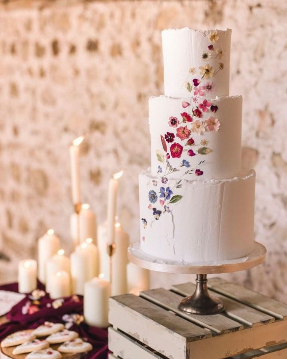 a chic and beautiful white textural wedding cake with edible flowers pressed creating an ombre effect just wows