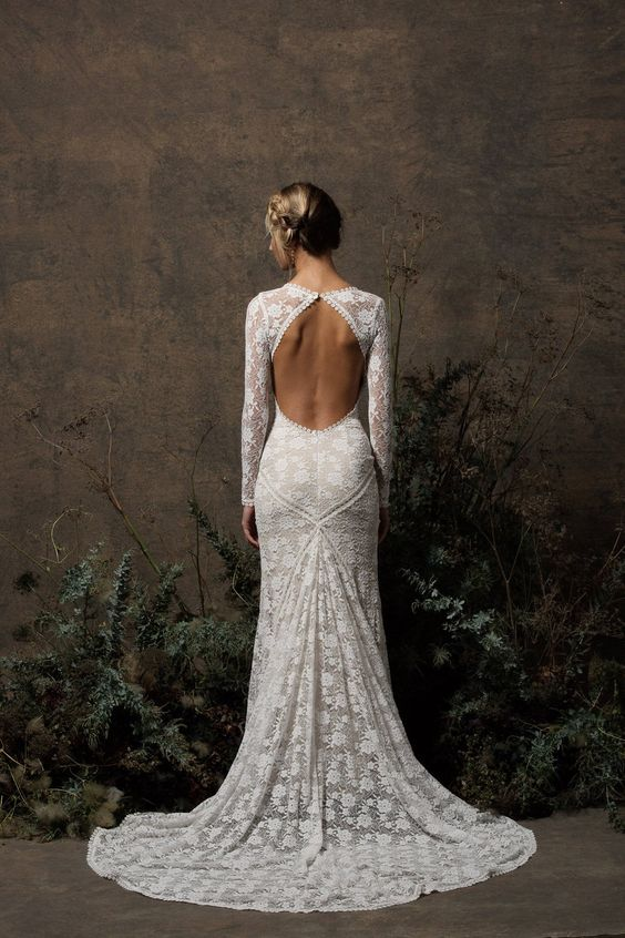 a chic boho lace mermaid wedding dress with a keyhole back, long sleeves, a high neckline and a short train is a lovely idea for a modern space