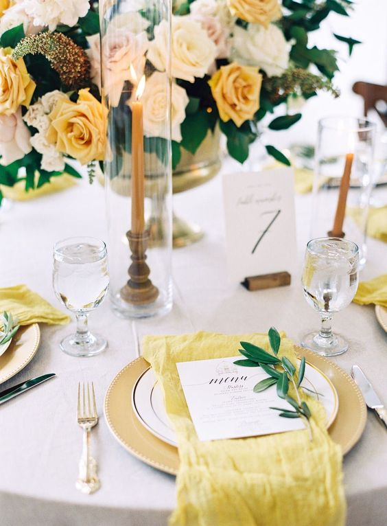 a chic spring wedding tablescape with a lush floral centerpiece, rust candles, lemon yellow napkins and yellow plates