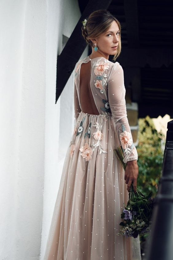 a dreamy floral embroidery A-line wedding dress with long sleeves and a pleated skirt and matching earrings