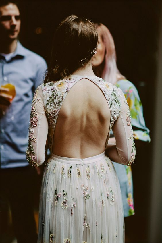 a floral embroidery A-line wedding dress with a keyhole back and chic colorful detailing and long sleeves for a summer bride