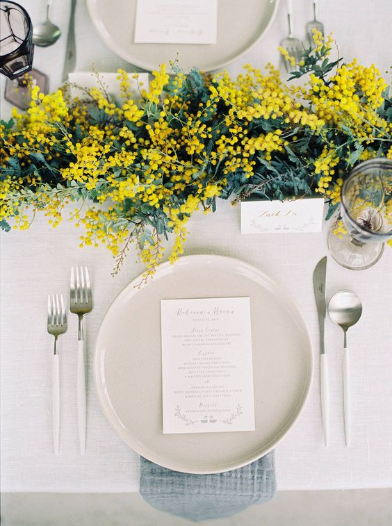 a fresh and sophisticated wedding tablescape with a mimosa and greenery runner, neutral plates, blue napkins