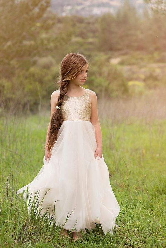 a glam flower girl with a gold sequin bodice and a layered skirt is a bright and shiny idea to try