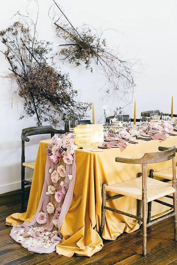 a jaw-dropping wedding tablescape with a mustard tablecloth, a pink runner with blooms, yellow candles and dried blooms