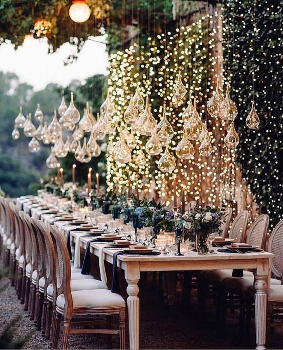 a lights wall and whimsically shaped glass candle holders over the table make the reception glam and very chic