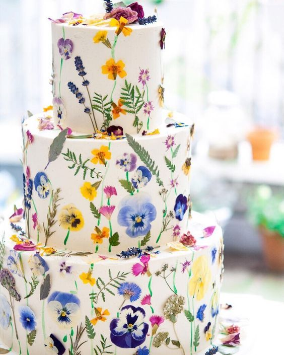 a lovely colorful wedding cake with lots of bright pressed flowers and leaves for a bright summer wedding