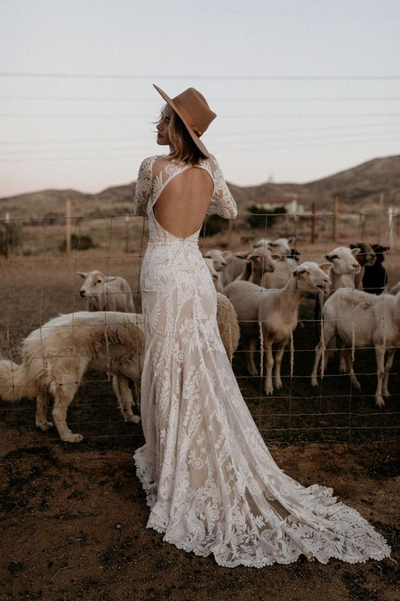 a lovely lace mermaid wedding dress with a keyhole back, long sleeves and a high neckline, a short train and a hat for a boho look