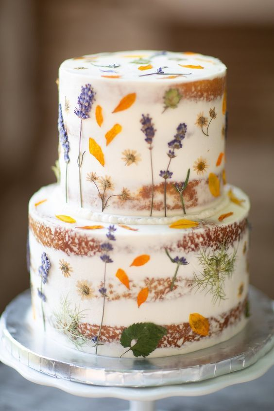 a lovely naked wedding cake with pressed flowers and leaves is great for a boho or relaxed flower filled wedding