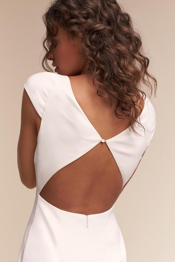 a minimalist wedding dress with a keyhole back and a cutout over it, with cap sleeves and a couple of buttons