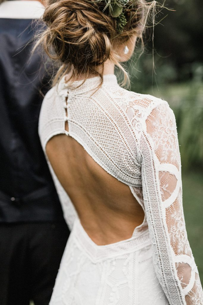 a modern boho lace fitting wedding dress with a keyhole back on buttons, long sleeves and a high neckline is a bold solution for a boho wedding