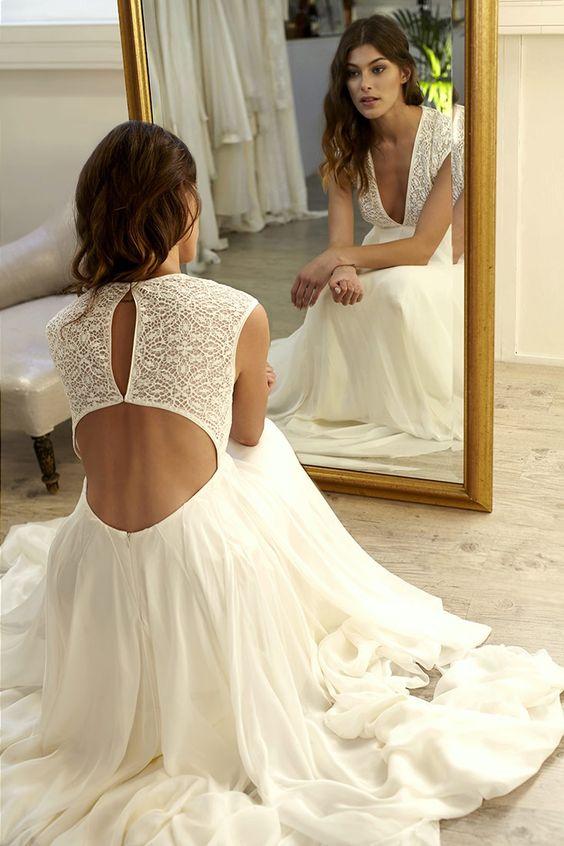 a modern romantic wedding dress with a boho lace bodice, a keyhole back, a deep neckline and a plain fully skirt with a train