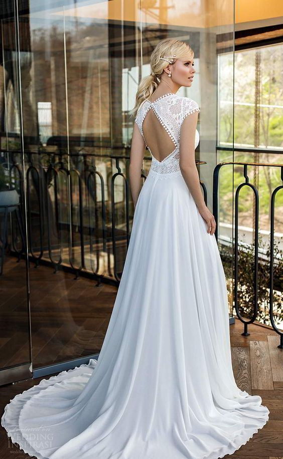 a modern wedding ballgown with a boho lace bodice, with a keyhole back, cap sleeves with tassels and a plain skirt with a small train