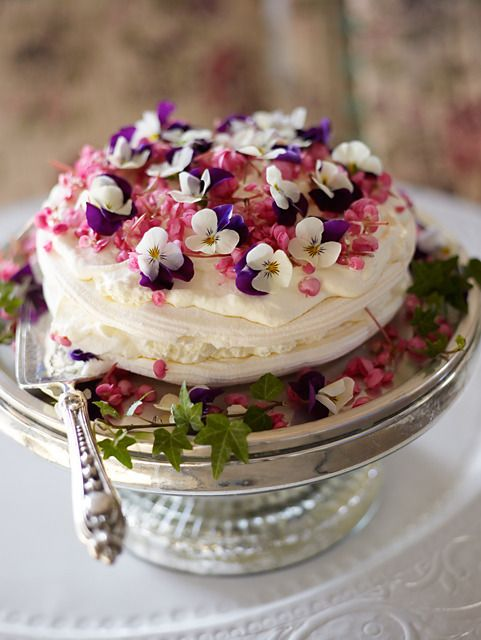 a pavlova wedding cake with edible pansies on top is an amazing cake for a garden wedding