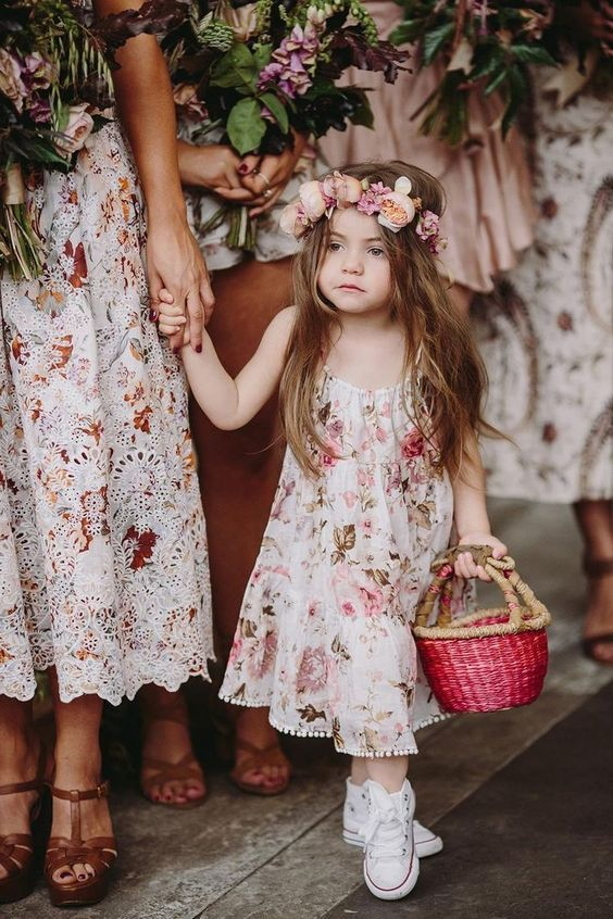 a pink A line floral dress with a pompom edge, white sneakers and a floral crown plus a pink basket for a summer or spring wedding