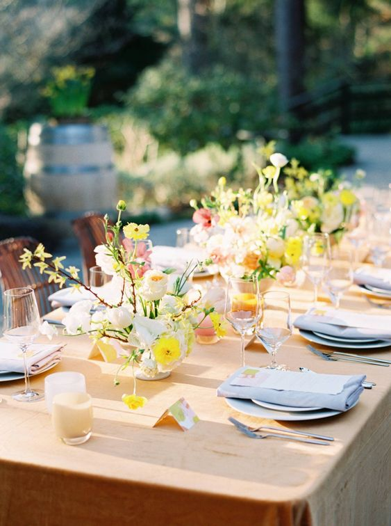 a refined spring wedding tablescape with a honey yellow tablecloth, bold yellow and neutral blooms, pink candles and blue napkins
