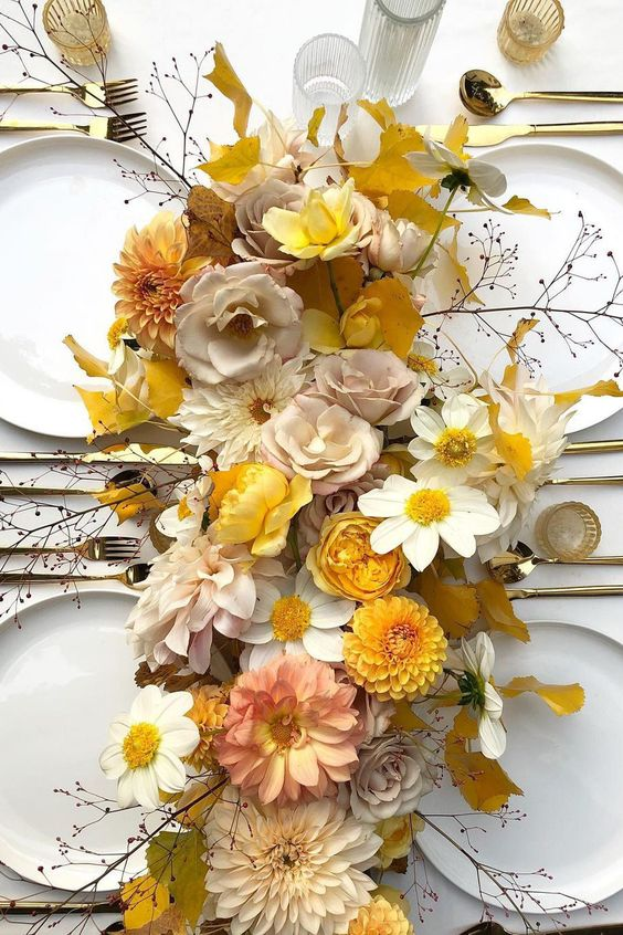 a refined wedding tablescape with yellow, peachy and white blooms, twigs, gold cutlery and white plates