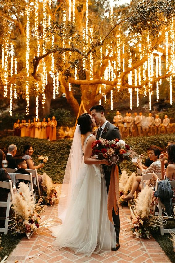 a romantic wedding ceremony space with lights hanging down from the tree make the space magical and gorgeous