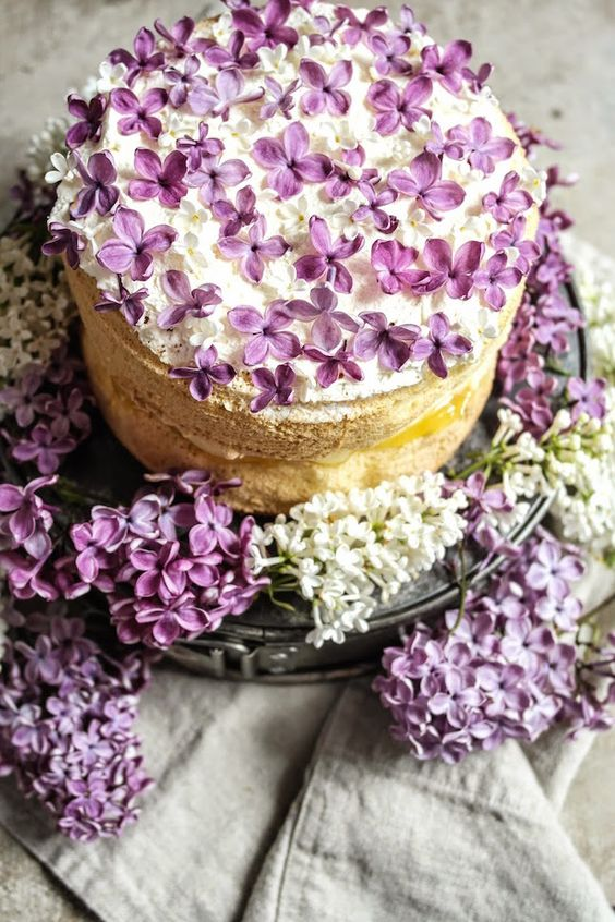 a simple naked wedding cake topped with fresh lilacs looks gorgeous and very romantic, ideal for a spring wedding
