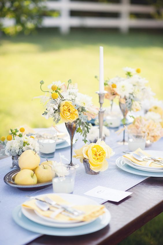 a sophisticated wedding tablescape with a printed runner, yellow blooms, candles and napkins and candles is chic