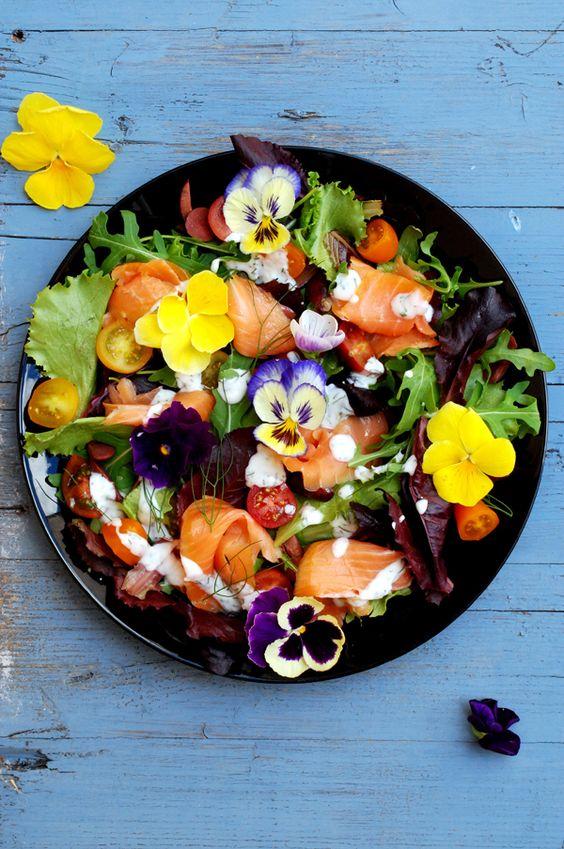 a summer wedding salad of smoked salmon, pansies, tomatoes, arugula, greenery and some yogurt sauce