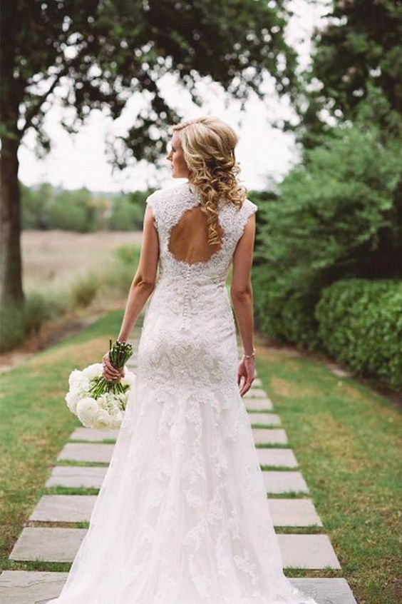a vintage lace mermaid wedding dress with a keyhole back, cap sleeves, a high neckline and a short train for a refined wedding