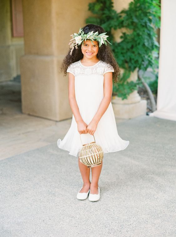 a white A-line midi flower girl dress with an embellished neckline, white flats and a greenert crown for a refined look