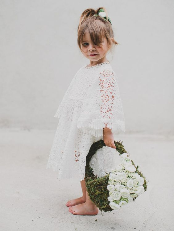 a white boho lace midi dress with bell sleeves, a high neckline and a moss and white bloom basket instead of a bouquet