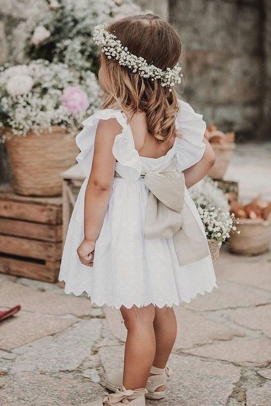 a white flower girl dress over the knee, with an open back and a large bow, sandals and a baby's breath crown