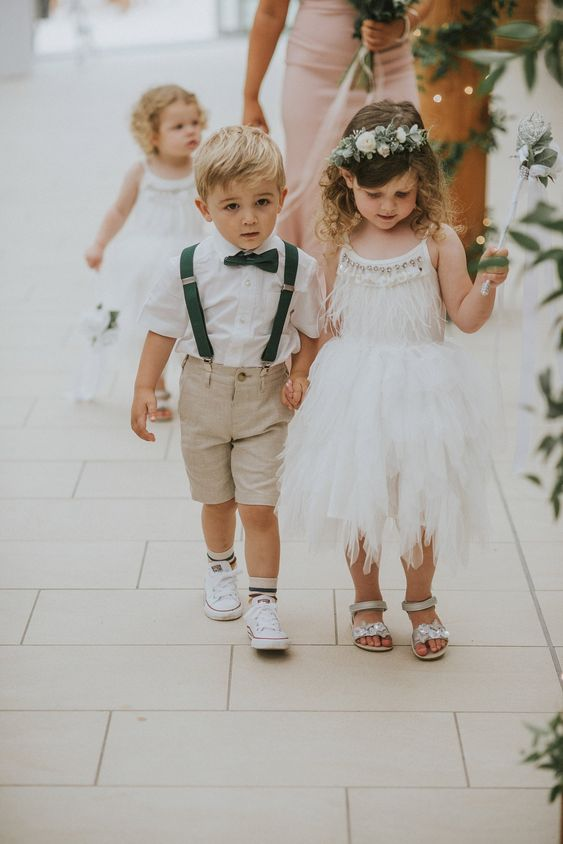 a white sleeveless flower girl dress with embellishments, fringe and a layered skirt plus embellished sandals