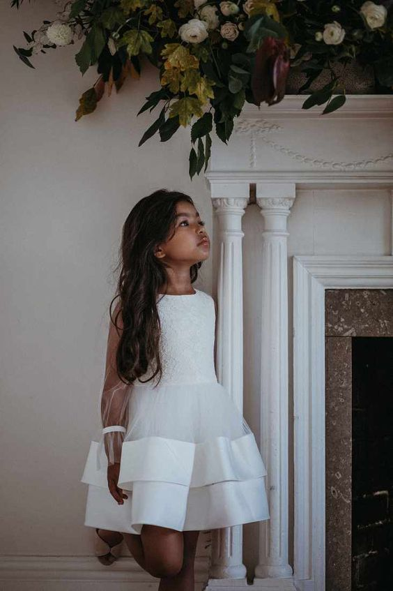 a white sleeveless knee flower girl dress with a lace bodice and a layered ruffle skirt is very stylish