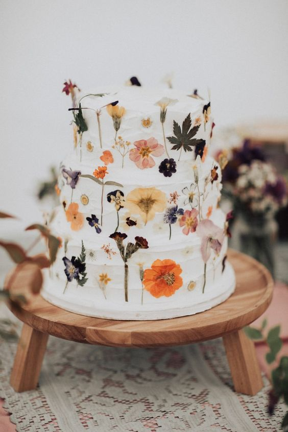 a white textural wedding cake with dried pressed blooms and leaves is wonderful for a spring or summer wedding