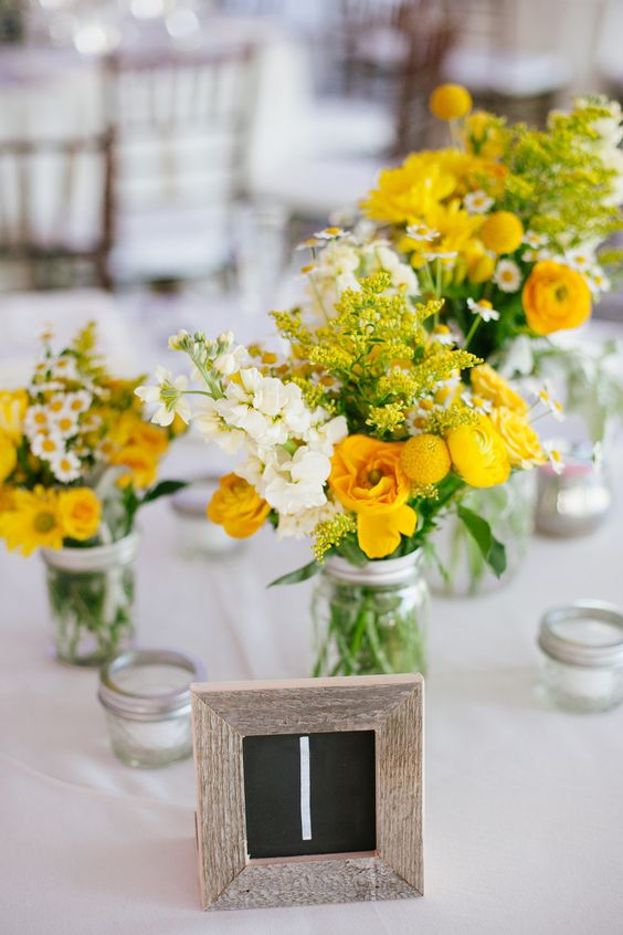 bold rustic wedding centerpieces of yellow and white blooms in jars and greenery are very cool