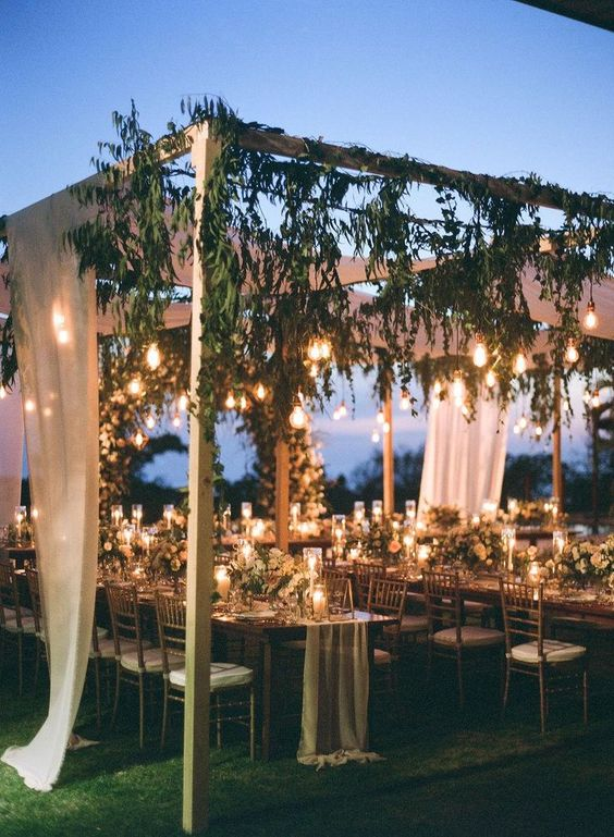 bulbs hanging down with greenery look more natural and hidden, and candles on the table add chic